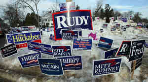 Campaign posters are seen in a snowbank outside a polling plac