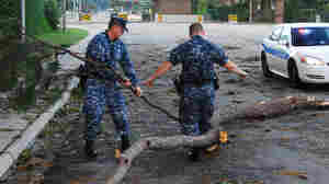 In this image provided by the U.S. Navy, sailors assigned to the base police department move debris from Hurricane Irene at one of the entrances to Joint Expeditionary Base Little Creek-Fort Story on August 28, 2011 in Virginia Beach, Virginia. The initial assessment shows the base suffered only minor damage and flooding from Hurricane Irene.