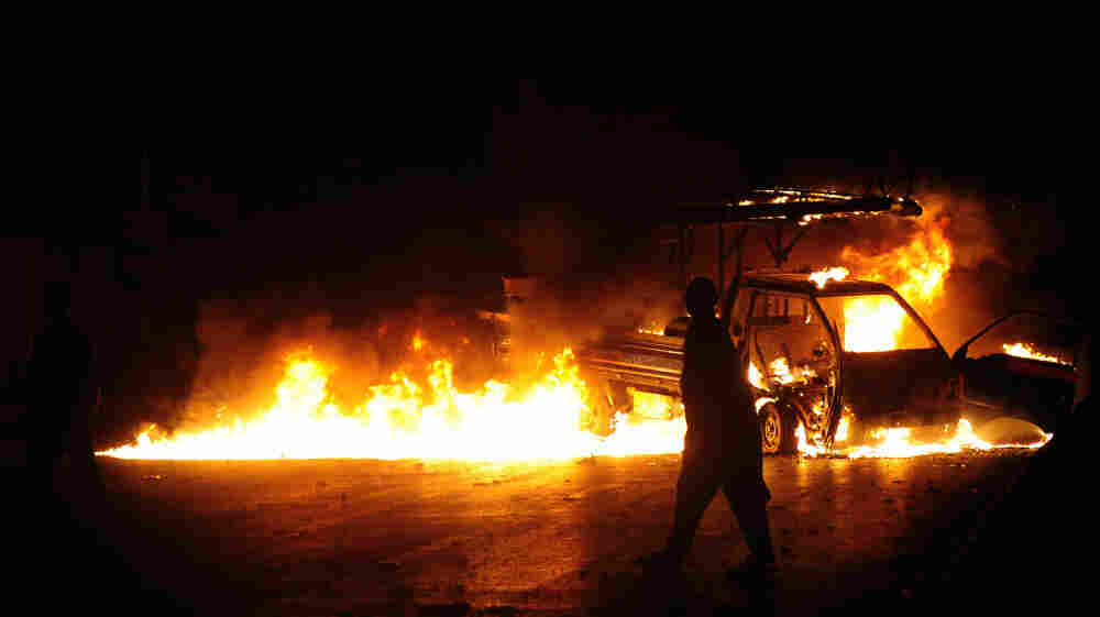 A man walks past a burning van in Karachi, Pakistan, on Aug. 4. Hundreds of extra paramilitary troops have been deployed in Pakistan's economic capital, which is struggling to end violence that has killed more than 300 people in recent weeks.