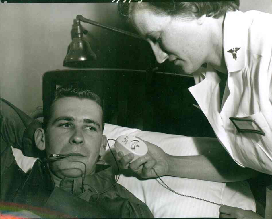 A nurse takes the temperature of a patient at Walter Reed using an electronic thermometer in 1954. The device, developed by Colonel George T. Perkins, an Army dentist stationed at Walter Reed, marked the first design change in a clinical thermometer since the mercury type was introduced in 1867.