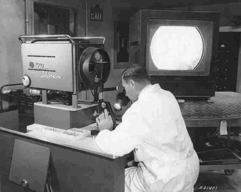 A Walter Reed researcher uses a color TV microscope developed by the center with RCA in 1957. The system allowed the researcher to broadcast slide images across the campus that could be used in a number of classrooms to teach students.