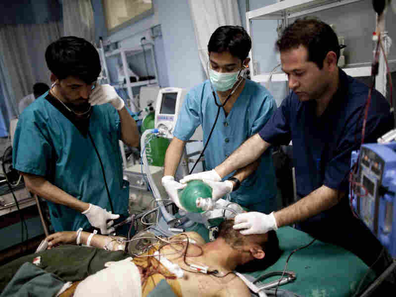 Doctors assist an injured Afghan soldier at the Davoud Khan military hospital in Kabul on April 23. U.S. medics have traveled to Afghanistan to help train 600 nursing students over a period of two years at a medical training center at the hospital.