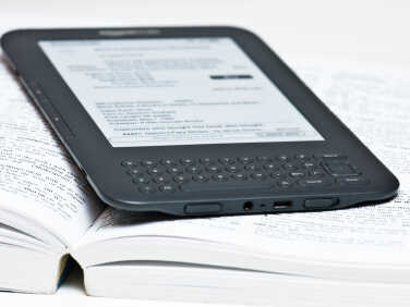An electronic reader lying on an open paper book.