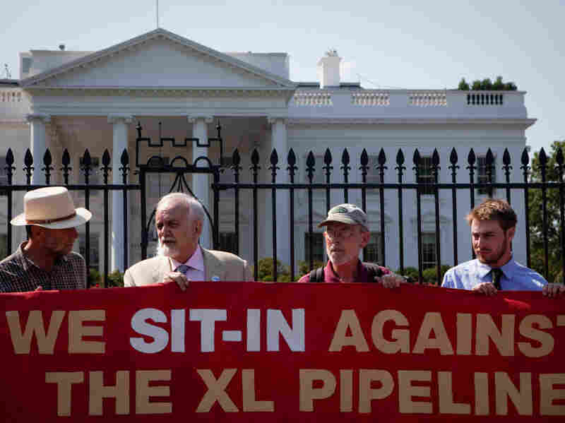 About 100 environmental activists protest the proposed Keystone XL pipeline in front of the White House on Thursday.