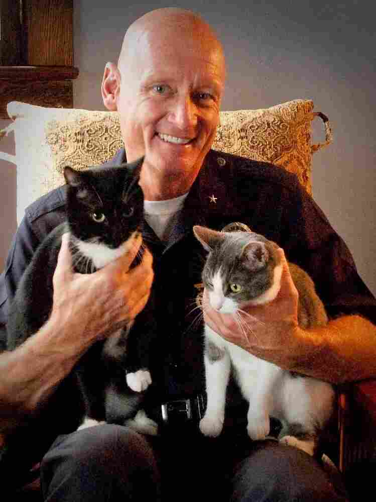 Cmdr. Andrew Smith poses with rescued cats Julia and Rocky. Smith, nicknamed Dr. Dolittle, helps rescue animals that are sold illegally in downtown Los Angeles.