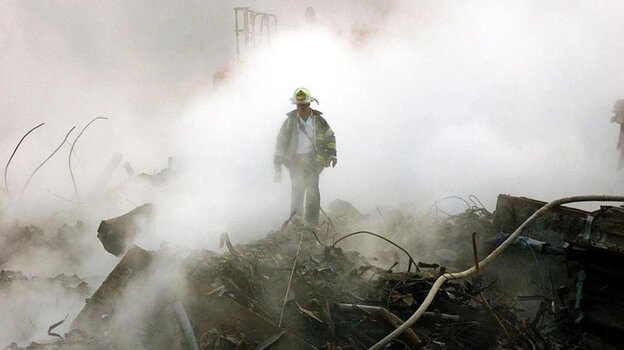 A fireman walks amongst the rubble and the smoldering wreckage of the World Trade Cen