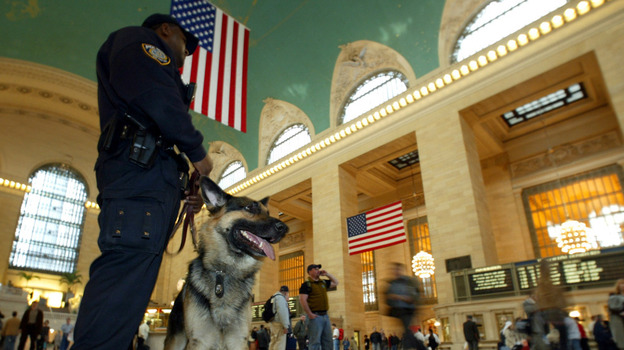 """A K-9 police officer and his partner, """"Bart,"""" patrol New York's Grand Central Terminal in 2003. L"""