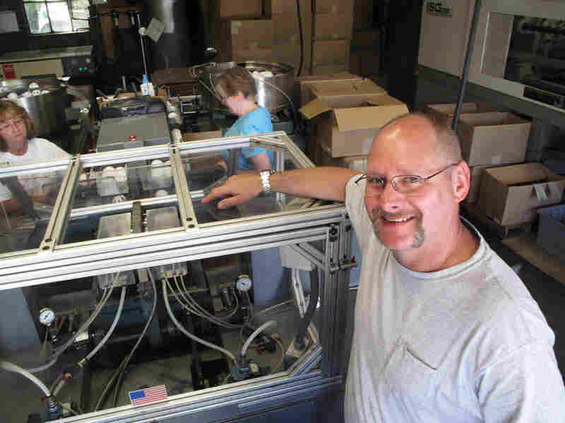 Stephen Mullany, who runs The Wiffle Ball Inc. with his brother David, poses in front of the machine that presses the two plastic ball halves together at a factory in Shelton, Conn. Mullany's grandfather invented the Wiffle Ball in the 1950s.