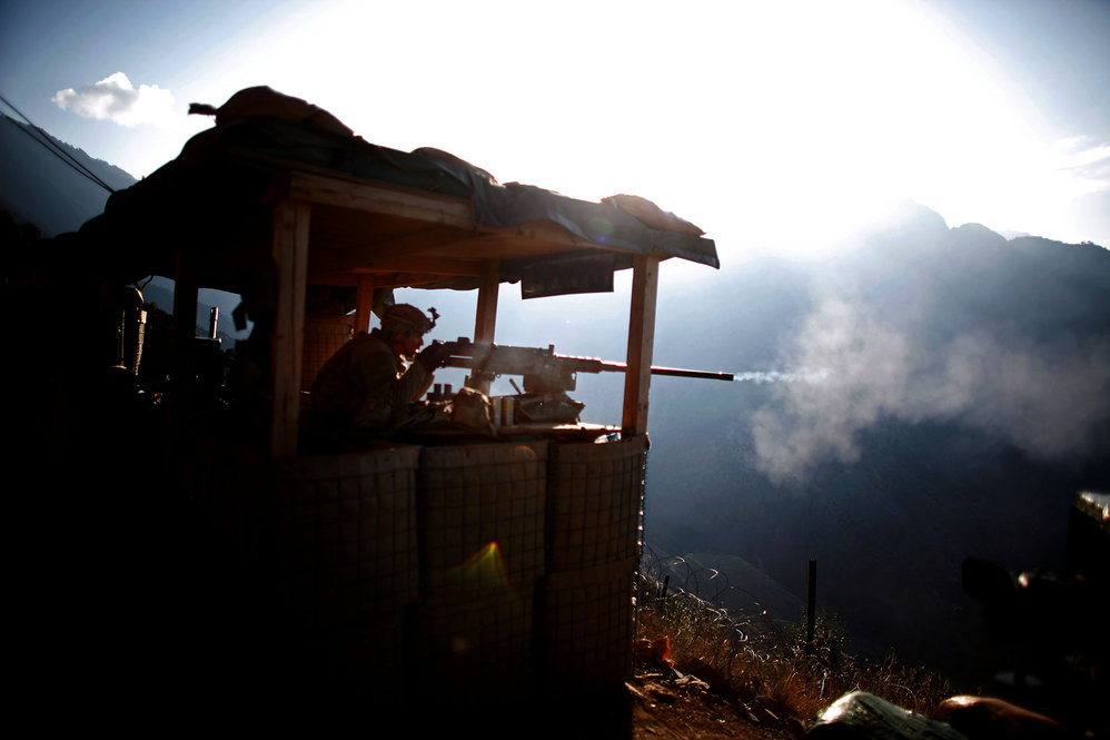 Pfc. Martinez fires a machine gun at an enemy fighting position, while insurgents fire at another American base in the valley bellow.