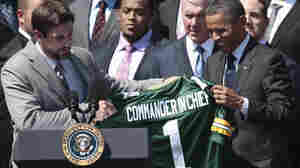 President Obama is presented with a Green Bay Packers football jersey by quarterback Aaron Rodgers (left) during a White House ceremony on Aug. 12 honoring the Super Bowl XLV champions.