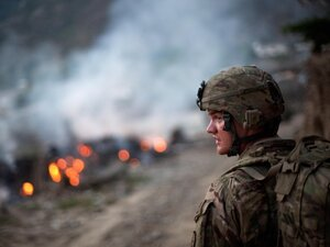 Army Pfc. Brayden Panttaja, 23, of Moscow, Idaho, walks past a pile of burning garbage while descending from a hilltop observation post at Combat Outpost Monti in Kunar province, Afghanistan, on Tuesday.
