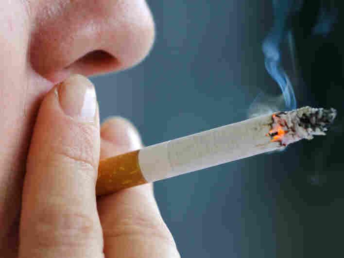 A woman puffs on a cigarette.