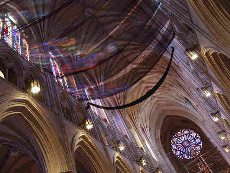 Light from stained glass windows shines onto safety nets that have been installed along the ceiling of the nave at the National Cathedral, as a precautionary measure after parts of the structure was damaged in an earthquake.