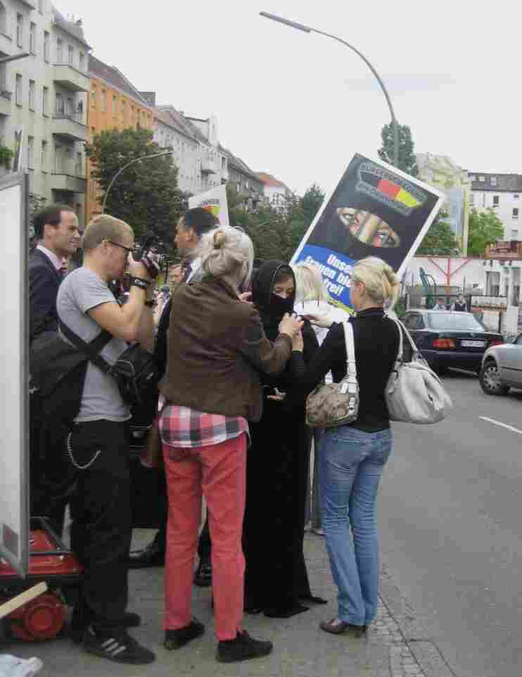Pro Deutschland supporters carry signs depicting a women in a niqab with jailhouse bars in front of the gap left for the eyes.