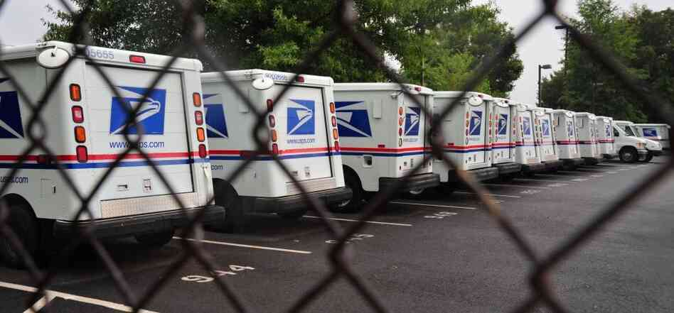 U.S. Postal Service mail delivery trucks sit idle at the Manassas post office in Virginia on Sept. 5.