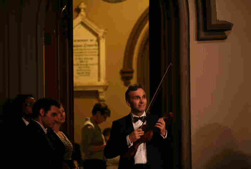 "Gil Shaham, violinist, watches the choir while waiting to perform during ""Remember to Love: Let Us Love One Another With A Sincere Heart."""