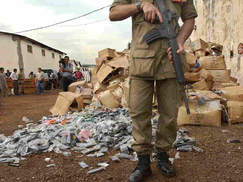 A police officer guards a stash of fake merchandise in Ciudad del Este,  Paraguay, the smuggler-ridden border town were Rotella sets part of his novel.