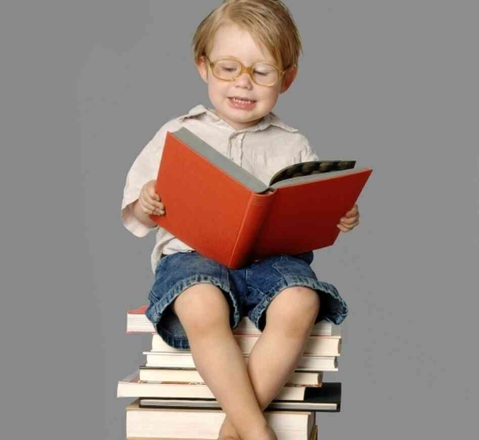 A boy reads, sitting on a stack of books.