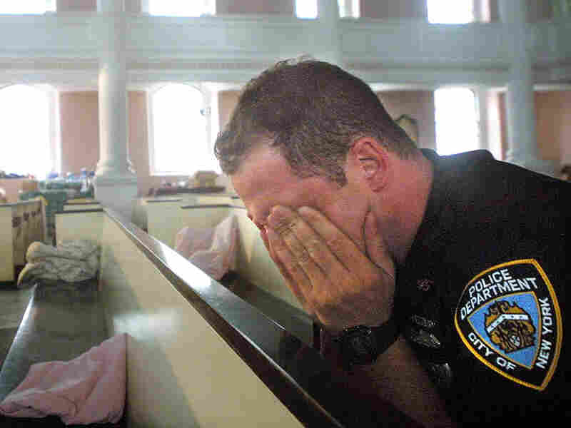 An NYPD police officer takes comfort in St. Paul's Episcopal Chapel, near the site of the World Trade Center attack, September 21, 2001.