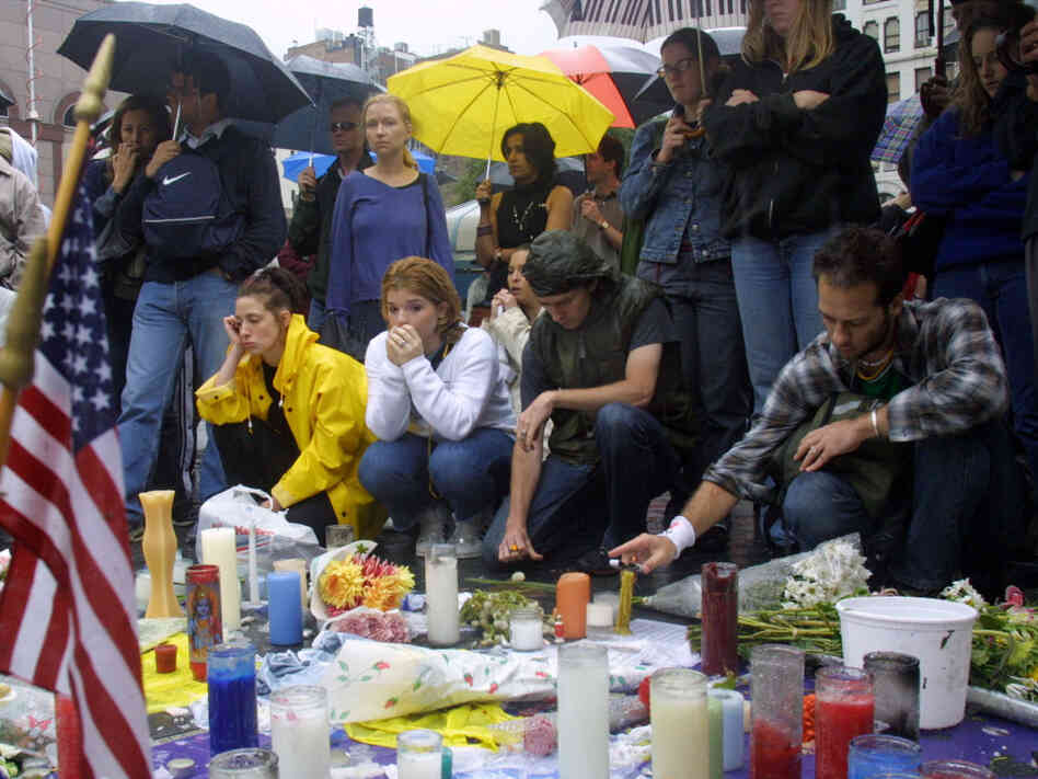 People mourn the victims of the World Trade Center disaster at a memorial in Union Square Park in New York City.