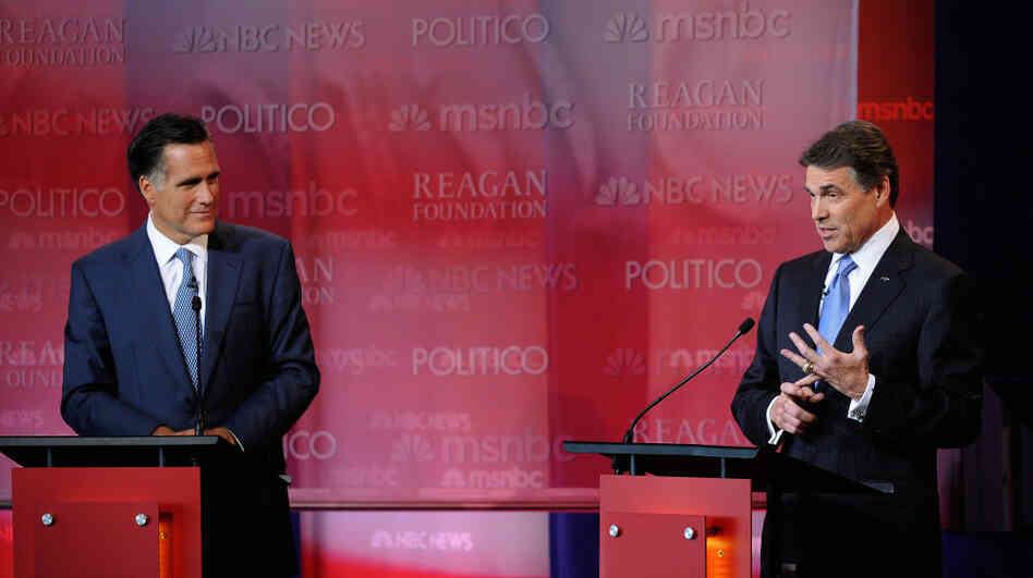 Republican presidential candidates Mitt Romney (L) looks at Texas Gov. Rick Perry as he speaks at the Ronald Reagan Centennial GOP Presidential Primary Debate.