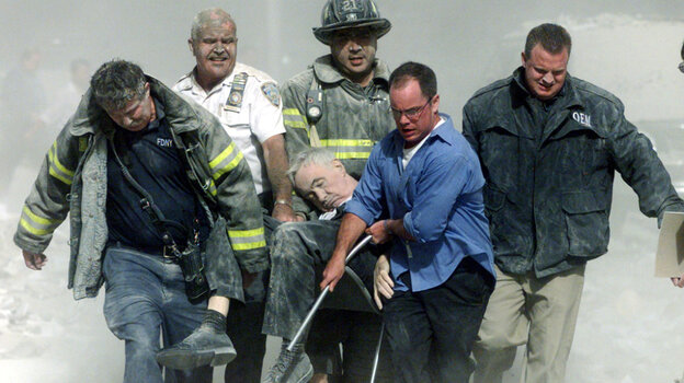 """A mortally injured Father Mychal Judge is carried out of the World Trade Center by first responders, including Bill Cosgrove (in white shirt). Cosgrove says, """"everybody you see in that picture was saved"""" from the North Tower's collapse, moments later."""