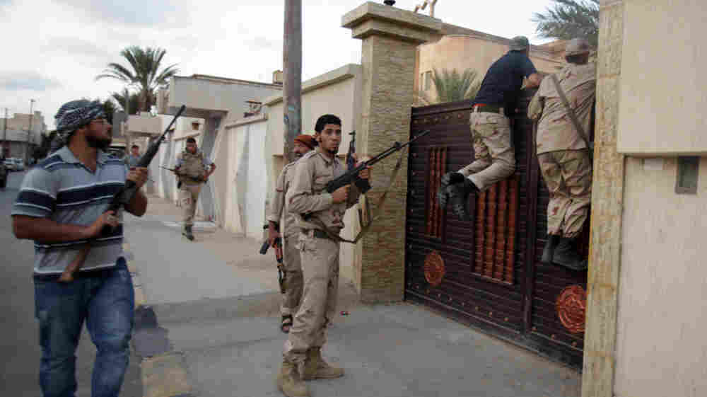 Libyan rebel fighters raid a house in Tripoli on Tuesday as they search for supporters of ousted leader Moammar Gadhafi. The rebel leadership is trying to get various rebel factions to work together to create a new government and security force.