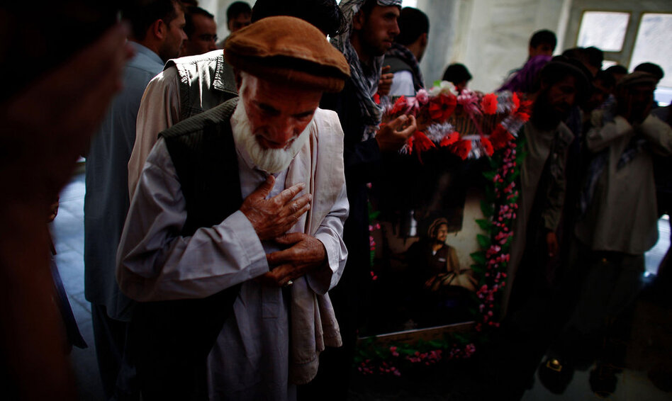 An Afghan man prays over Massoud's grave. Even today, posters of Massoud still adorn shops in the country's north. (NPR)