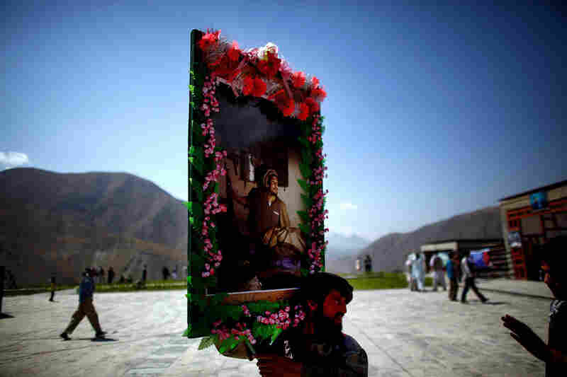On Sept. 9, 2001, al-Qaida agents assassinated Afghan resistance leader Ahmad Shah Massoud, the opening gambit in the terrorist group's Sept. 11 plan. Ten years later, on the anniversary of Massoud's death, a man carries a photo of Massoud after visiting his tomb and shrine in Afghanistan's Panjshir Valley.