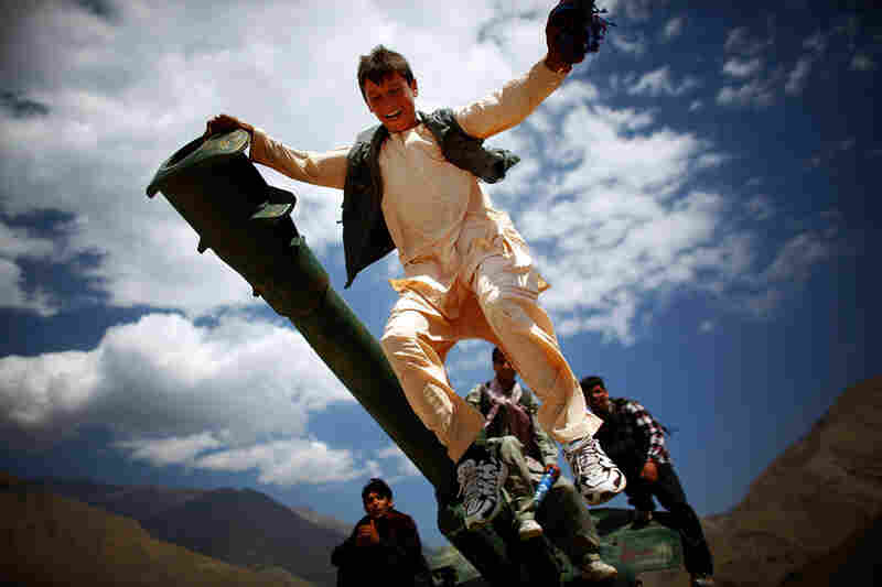 Afghan boys play on an old Soviet artillery gun outside the shrine.