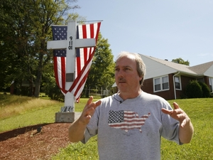 Rick King, who was assistant fire chief of Shanksville, Pa., on Sept. 11, 2001, stands near a cross made from steel from the World Trade Center, outside the fire station in Shanksville on July 14. He was one of nine people to tell NPR what Sept. 10 was like, the day before the horrible events of Sept. 11.
