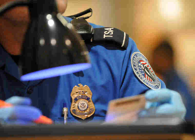 A TSA agent checks the identification of airline passengers at Hartsfield-Jackson Atlanta International Airport.