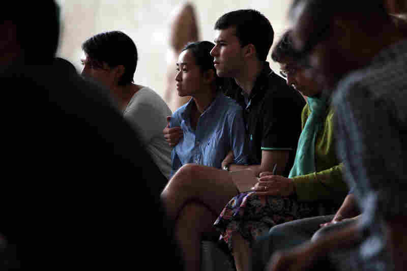 Members of the audience listen to Remembering September 11, a concert by the Wordless Music Orchestra conducted by Ryan McAdams presented at The Temple of Dendur in The Sackler Wing at The Metropolitan Museum of Art in Manhattan, NY on September 11, 2011.