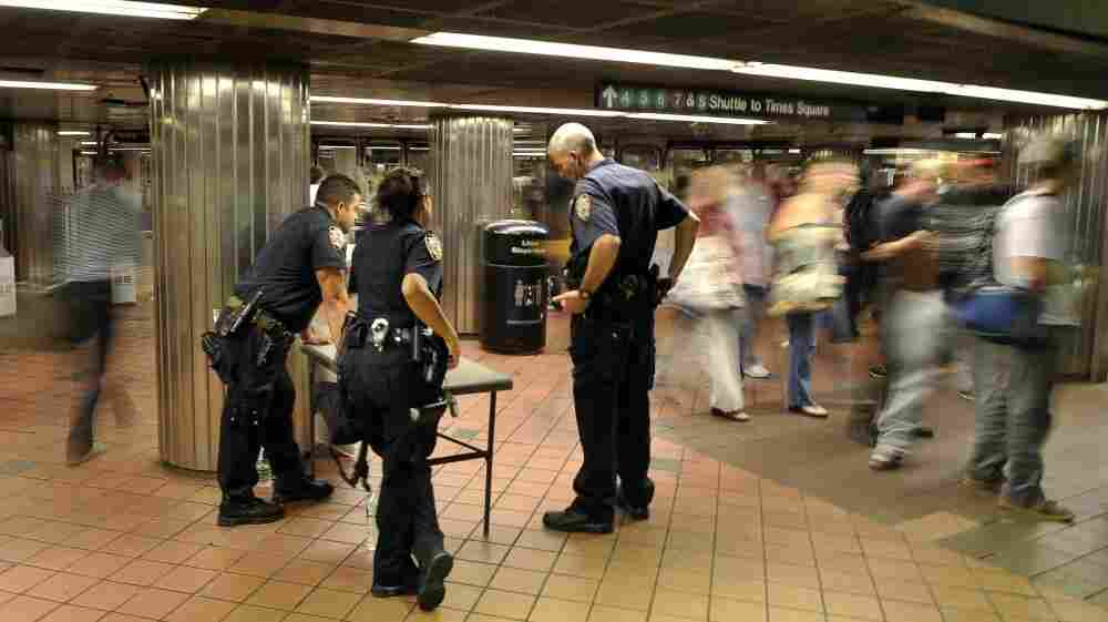 Police officers watch travelers at the entrance of the Grand Central subway terminal in New York on  Thursday. Security measures around the city were increased two days before the 10th anniversary of the Sept. 11 attacks.