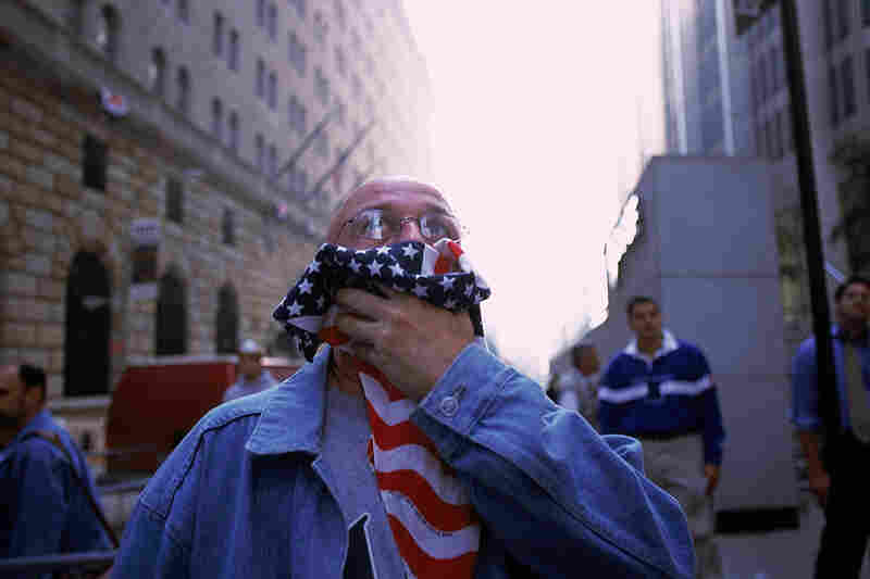 A man covers his mouth to keep out the acrid air.