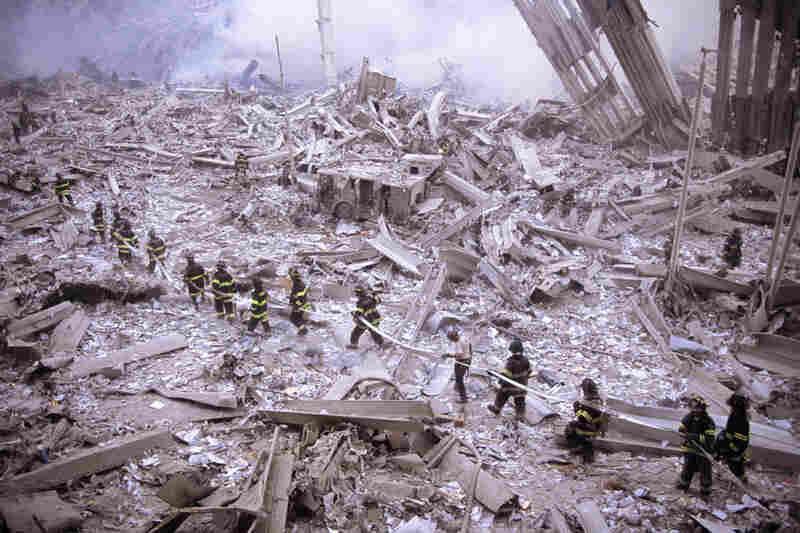 Firefighters carry hose across wreckage after collapse of the World Trade Center's twin towers.