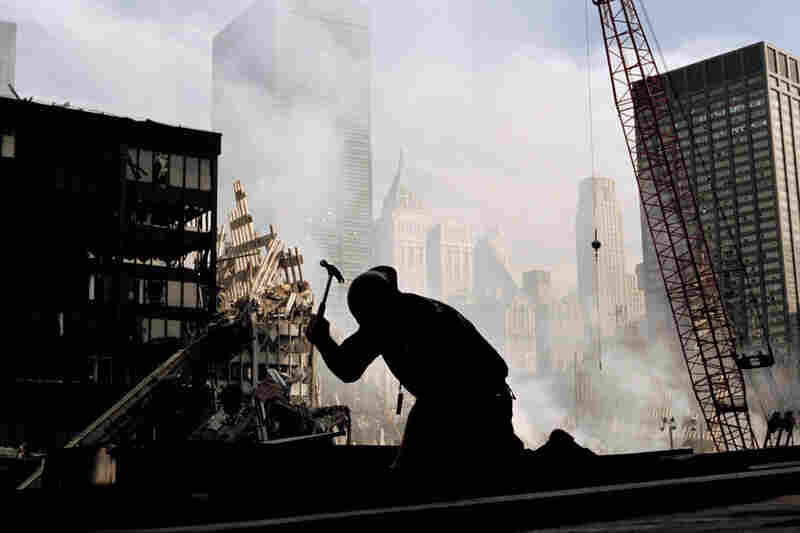 A lone construction worker hammers away at the wreckage of the World Trade Center.
