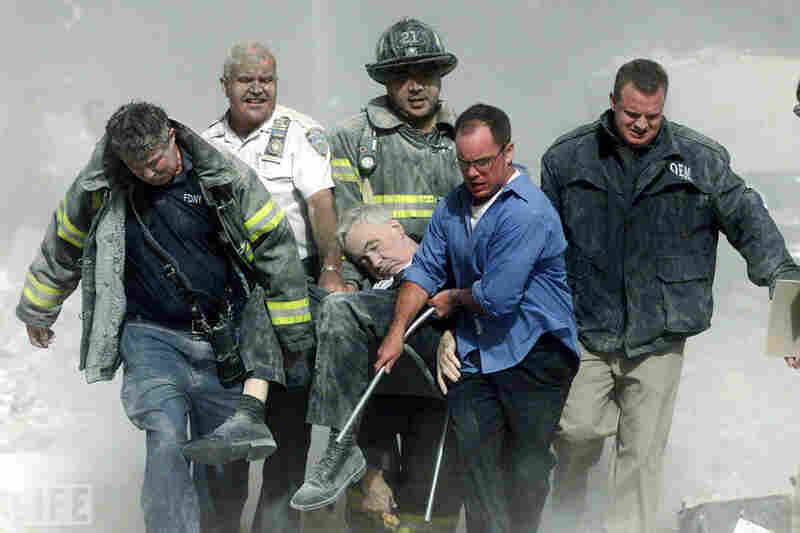 """Rescue workers carry mortally injured New York City Fire Department chaplain Mychal Judge from the wreckage after he was killed by falling debris while administering last rites to another victim. A Roman Catholic priest, a recovering alcoholic, a gay man, and a spiritual adviser and trusted friend to countless firefighters through the years, """"Father Mike"""" was the first recorded victim of the Se..."""