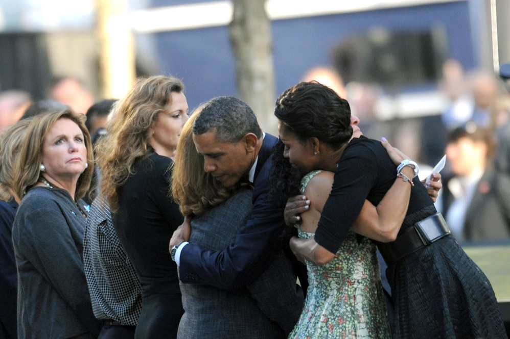 President Barack Obama and first lady Michelle Obama hug people during ceremonies at the 9/11 Memorial.