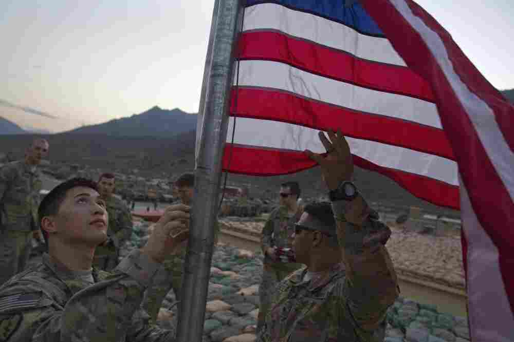 Capt. Cameron Mays, 27, of Marion, Ky., left, and Spc. Angel Batista, 26, of Bloomingdale, N.J., with the U.S. Army's 25th Infantry Division, 3rd Brigade Combat Team, 2nd Battalion 27th Infantry Regiment based in Schofield Barracks, Hawaii, raise a new American flag to commemorate the tenth anniversary of the 9/11 attacks at Forward Operating Base Bostick in Kunar province, Afghanistan.