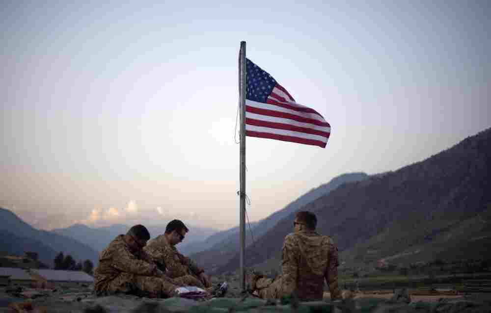 Spc. Angel Batista, 26, left to right, of Bloomingdale, N.J., Spc. Jacob Greene, 22, of Shreveport, La., and Sgt. Joe Altmann, 26, of Marshfield, Wisc., sit beneath a new American flag just raised to commemorate the tenth anniversary of the 9/11 attacks Sept. 11, 2011 at Forward Operating Base Bostick in Kunar province, Afghanistan.