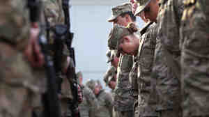 U.S. soldiers pray during the an anniversary ceremony of the terrorist attacks on September 11, 2001 at Bagram Air Field, Afghanistan.