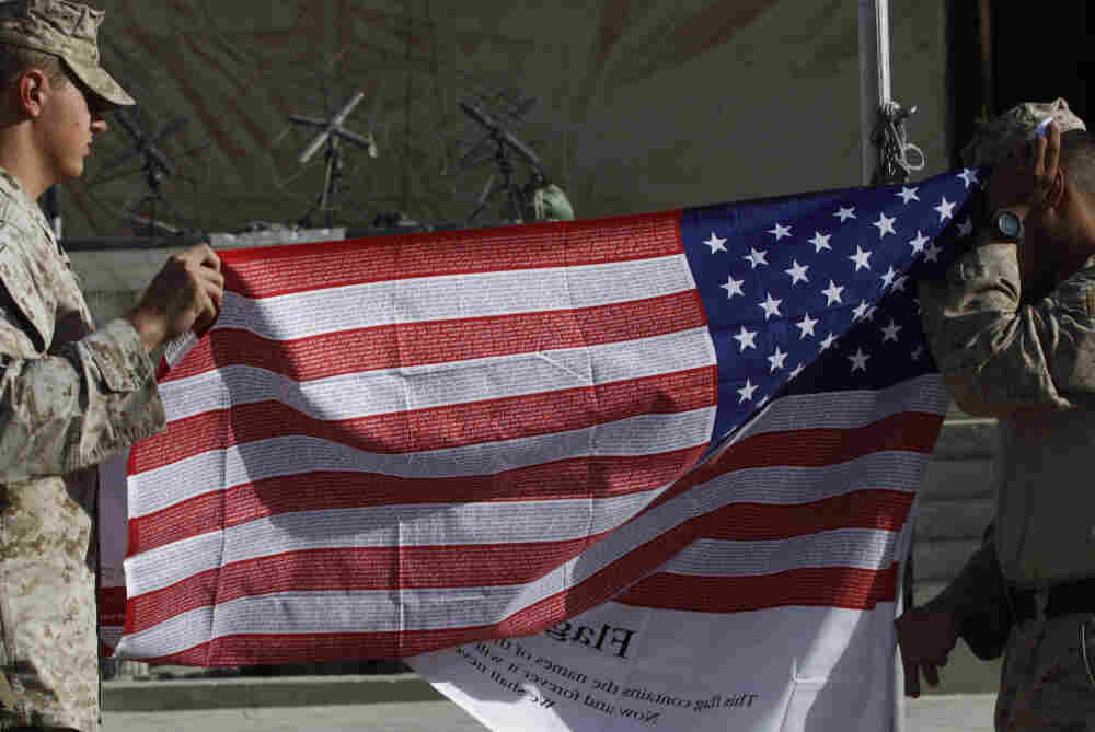 U.S. Marines fold a memorial American flag imprinted with the names of the Sept. 11, 2001 attack victims, after raising and lowering it to mark ten years since the attack, at Forward Operating Base Jackson, in Sangin, Helmand province.
