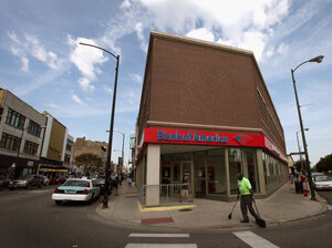 A worker sweeps in front of a Bank of America branch in Chicago.  On Monday, the bank announced plans to lay off 30,000 employees, or about 10 percent of its staff, over the next few years.
