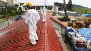 Workers decontaminate the roof of a kindergarten about 12 miles from the crippled Fukushima nuclear pla