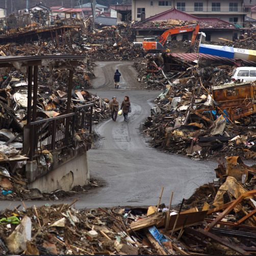 Local residents walk among debris in Kesennuma, Japan, on March 31, just weeks after the quake and tsunami.
