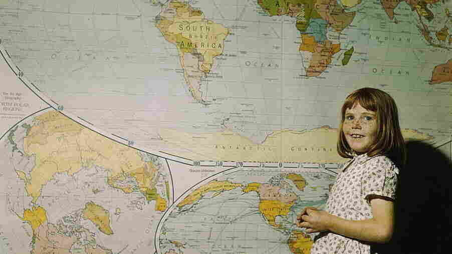 A schoolgirl in Texas stands in front of a map in 1943.