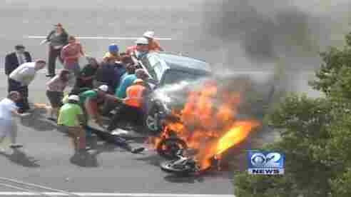 People rushed to help. They lifted the car so that the motorcyclist could be pulled free.