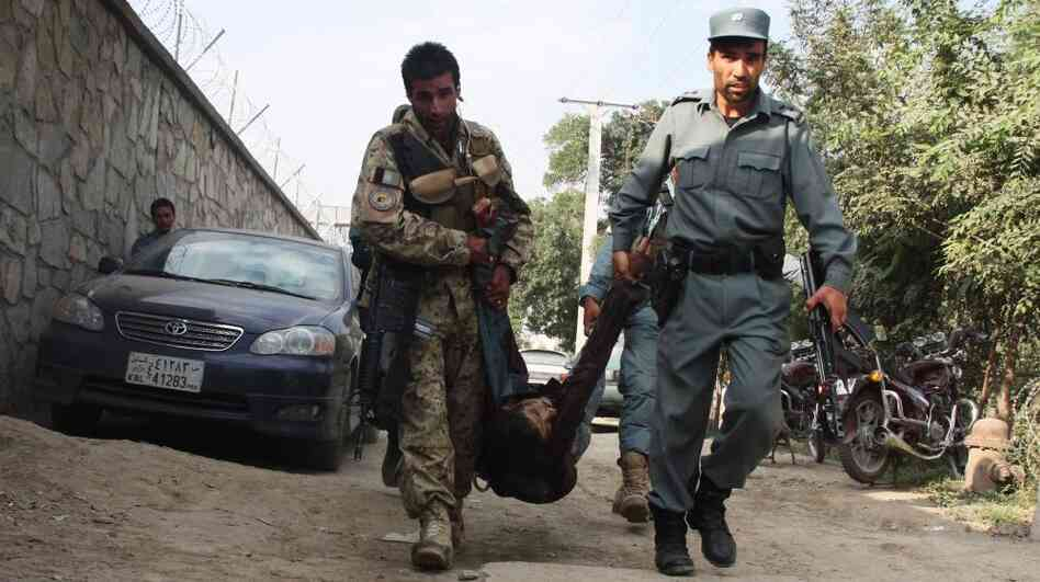 Afghan security officials carry the body of a fallen comrade after several armed Taliban militants launched attacks in Kabul, Afghanistan, on Tuesday.