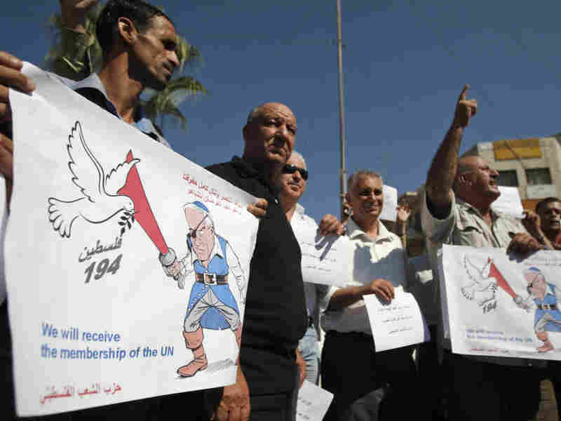 Palestinians hold signs depicting Israel's Prime Minister Benjamin Netanyahu as a pirate during a demonstration supporting the Palestinians' bid for statehood, in the West Bank city of Ramallah on Monday.